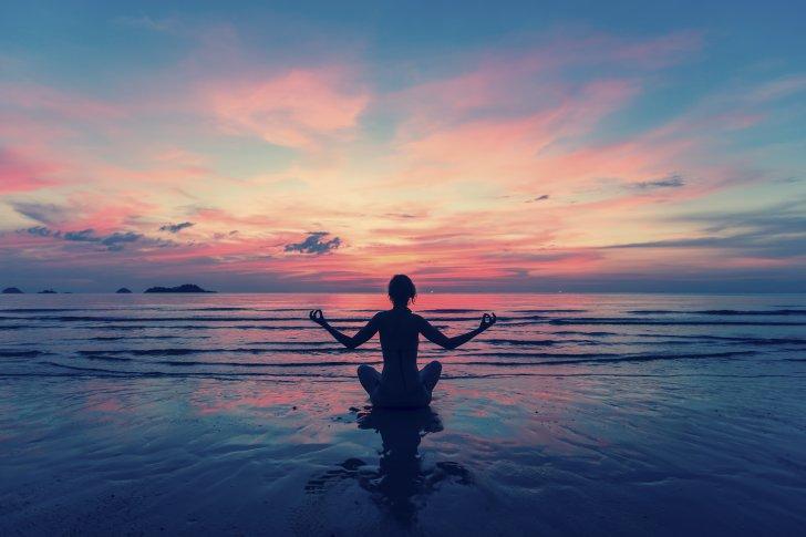 לנשום ולהצליח - Woman doing meditation near the ocean beach